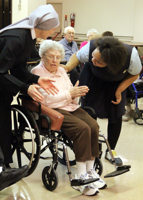Sr. Veronica Proffitt and Monique Allen dance along with a resident of Holy Family Home.