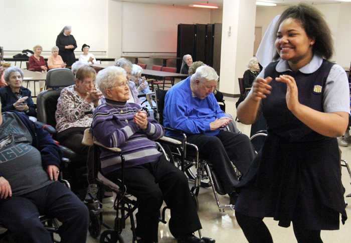 Monique Allen, class of '16, gets the crowd going when students from her school visited ederly reseidents of Holy Family Home for Catholic Schools Week.