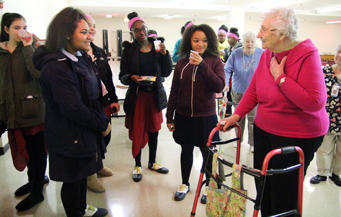 Students from John W. Hallahan Catholic Girls' High School chat with residents of Holy Family Home during a visit they made for Catholic Schools Week.