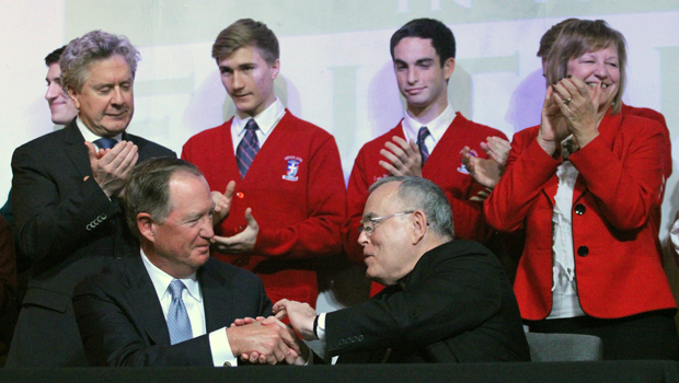 Faith in the Future Foundation's board chairman Edward Hanway shakes hands with Archbishop Charles J. Chaput after they signed an agreement Feb. 4 at Archbishop Ryan High School to extend the schools management partnership for six more years . Also shown along with Ryan students are Samuel Casey Carter (left), CEO of the foundation, and Archbishop Ryan President Denise LePera. (Photo by Sarah Webb)