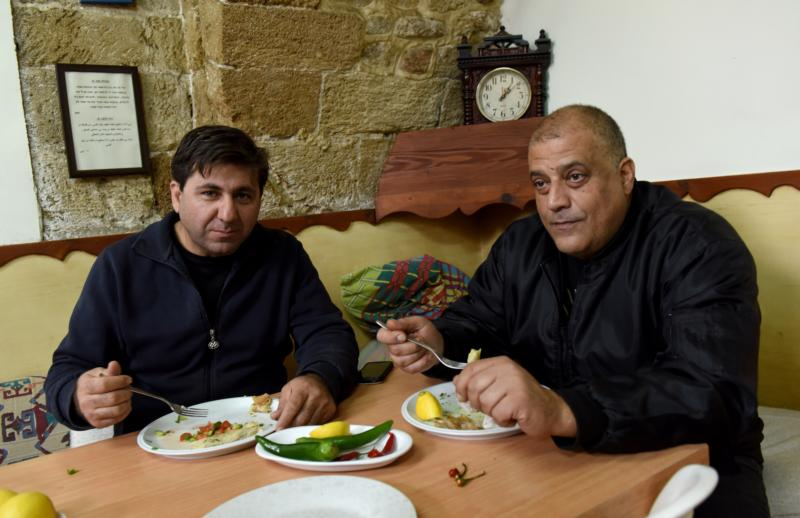 Israeli Arab volunteer Geris Deeb and Elias Khoury, 43, who is doing community service, eat lunch in the communal dining room Jan. 7 at the House of Grace in Haifa, Israel. (CNS photo/Debbie Hill)