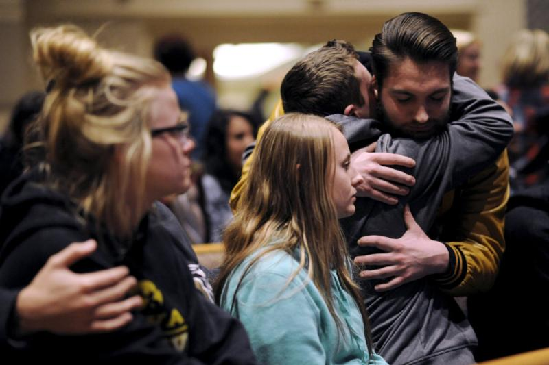 People hug at a vigil after six people were killed in a random shooting in Kalamazoo, Mich., Feb. 21. Kalamazoo Bishop Paul J. Bradley decried the  shootings and offered prayers for victims at a Feb. 22 Mass. (CNS photo/Mark Kauzlarich, Reuters)