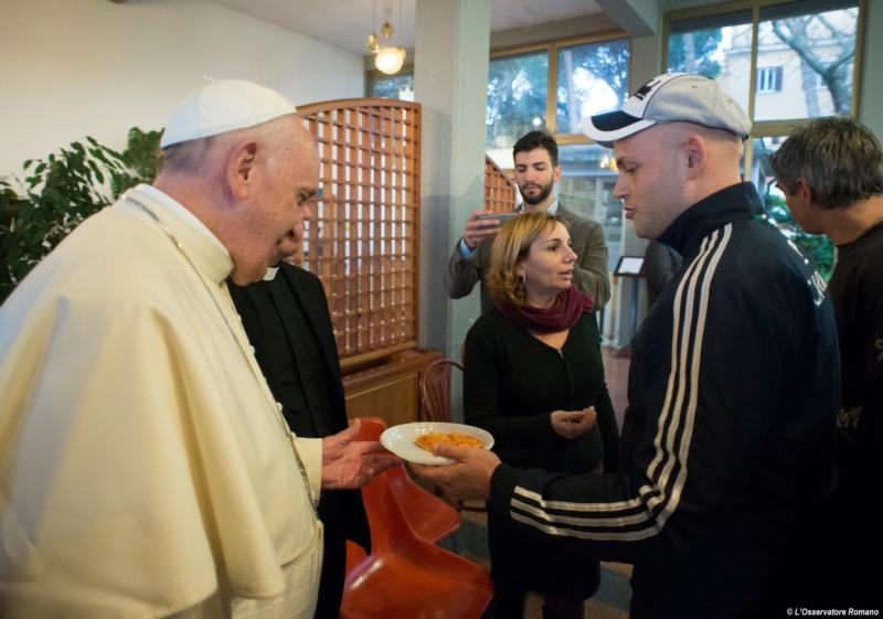 Pope Francis accepts a slice of pizza from a patient at the San Carlo community.