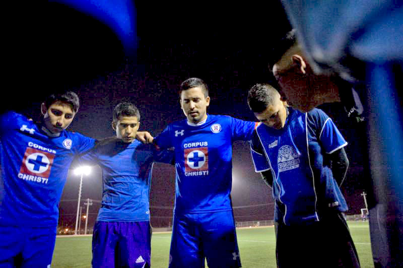 Esteban Gabriel Alanis, 23, right center, prays with members of his parish's soccer team before a Jan. 30 game in Ciudad Juarez, Mexico. Alanis, a former gang member, coordinates the youth outreach program at Corpus Christi Parish, which is in a working-class neighborhood. (CNS photo/David Maung)
