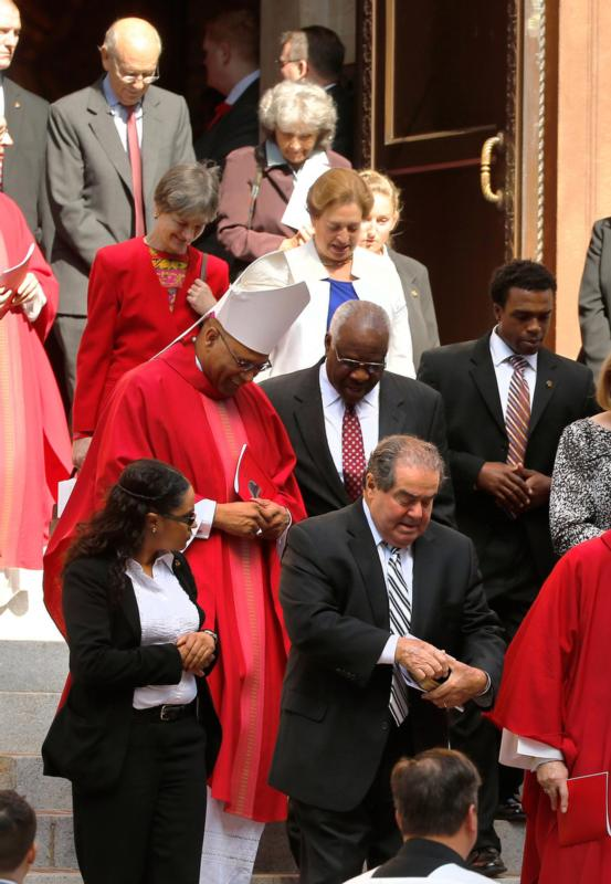 Washington Auxiliary Bishop Martin D. Holley, in red vestments, chats with U.S. Supreme Court Justice Clarence Thomas following the annual Red Mass at the Cathedral of St. Matthew in Washington Oct. 5. Also pictured is U.S. Supreme Court Justice Antonin Scalia, lower center right. The Mass traditionally marks the start of the court year, including the opening of the Supreme Court term. (CNS photo/Jonathan Ernst, Reuters)