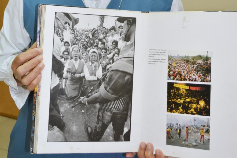 Sister Porferia Ocariza, a member of the Daughters of St. Paul, holds a book on the People Power uprising in the Philippines 30 years ago to oust dictator Ferdinand Marcos.  She is still recognized today for her stunned expression, left image, as military tanks approached. (CNS photo/Simone Orendain)