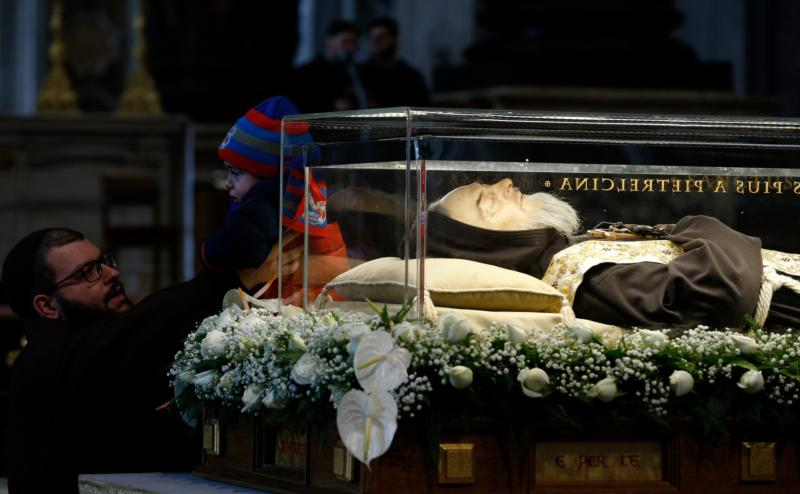 A child is lifted to come into contact with the glass case containing the body of St. Padre Pio in St. Peter's Basilica at the Vatican Feb. 6. The bodies of St. Padre Pio and St. Leopold Mandic were brought to Rome at the request of Pope Francis for the Year of Mercy. (CNS photo/Paul Haring)