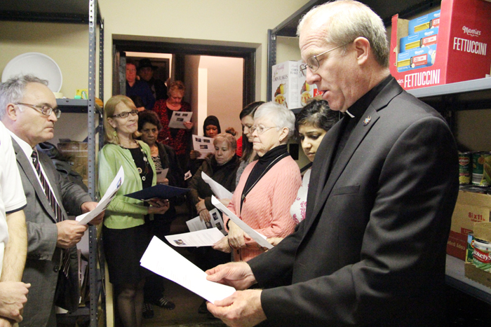 Father Thomas Higgins, pastor of Holy Innocents Parish in Philadelphia that is served by the St. Joan of Arc food cupboard, leads a prayer during the CRS Rice Bowl kick-off event at the small cupboard in the city's Frankford section Feb. 4. (Sarah Webb)