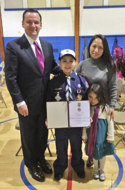 Boy Scout Robert Ritchie stands with his parents, Robert F. and Lisa V. Ritchie, and little sister Allison, as he displays his Medal of Merit award from the Boy Scouts of America, one of only 250 recipients each year nationwide.