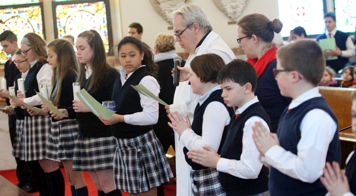 Father Joseph Maloney, pastor, prays along with students of Saint Aloysius School.