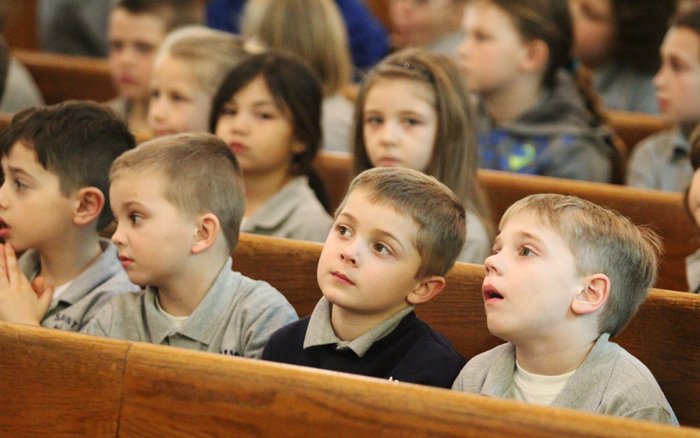 Pre-K students through 4th grade pray in their pews as upperclassmen line the church as a human rosary.