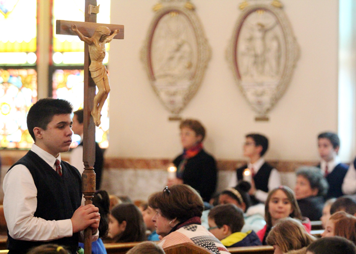 Seventh grader Alex Lohr holds the crucifix for the living rosary prayed by Saint Aloysius School for Catholic Schools Week.