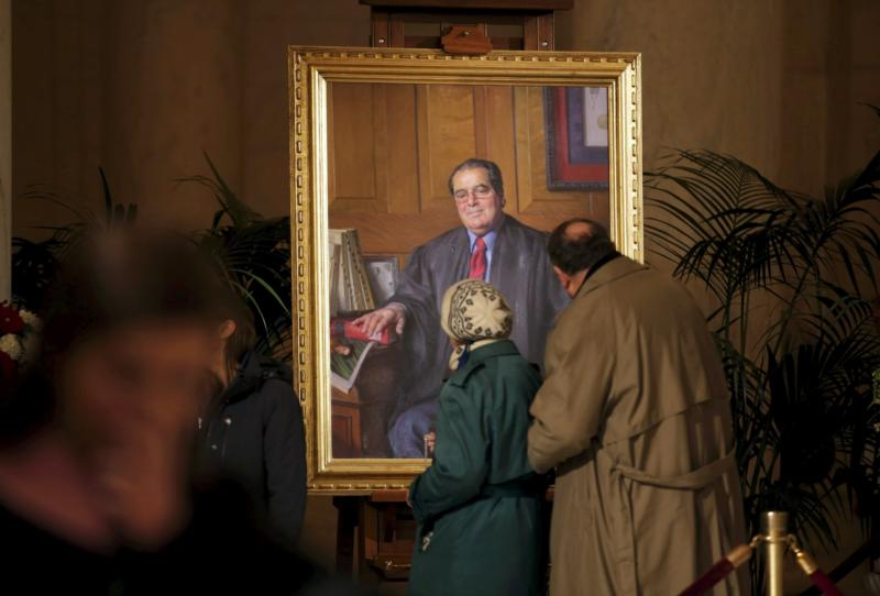 Members of the public pause to look at a portrait of the late Justice Antonin Scalia while his casket lay in repose in the Great Hall of the Supreme Court in Washington Feb. 19. (CNS photo/Carlos Barria, Reuters)