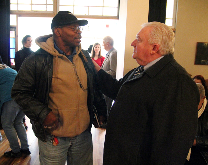 Melvin Fullwood chats with John Wagner as he waits for his number to be called to fill out an application for Saint Francis Villa.