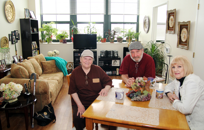 Residents of Nativity B.V.M. Place, Theresa Beckowski, Francis Hyduk and Mildred Roman, enjoy a cup of coffee in a resident's apartment, one of 63 units in the new senior housing facility of archdiocesan Catholic Health Care Services. (Photo by Sarah Webb)