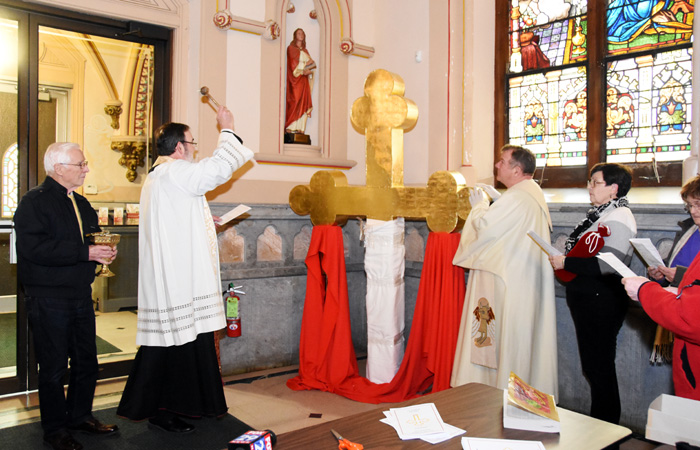 Msgr. Kevn Lawrence, left, blesses the refurbished gold cross that was replaced atop the bell tower of St. John the Baptist Church in Manayunk on Monday, Feb. 8.  (Photo by Sabina Pierce)