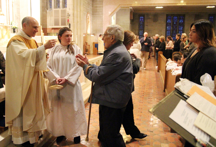 Pastor Father Thomas Sodano distributes Holy Communion.