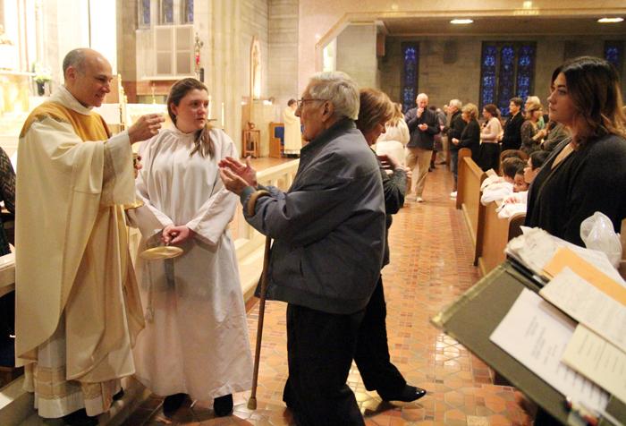 Pastor Father Thomas Sodano distributes Holy Communion.