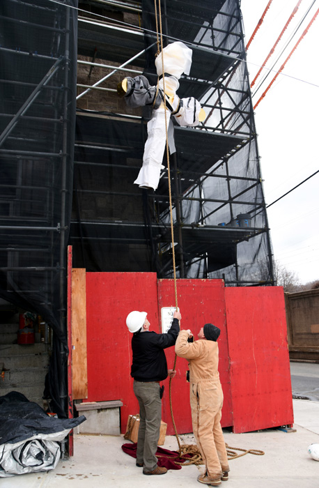 The cross is hoisted past the scaffolding at St. John's to rise 208 feet above the ground. (Photo by Sabina Pierce)