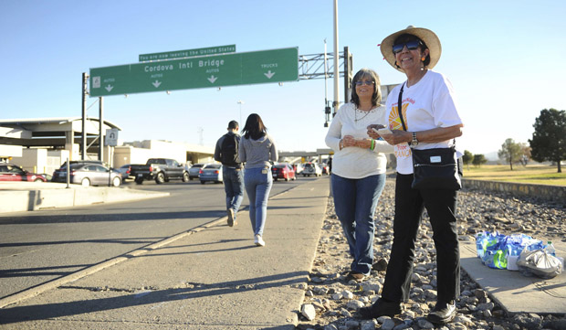 Cristina Varga and Eina Holder hand out water and prayer cards to pilgrims crossing the border Feb. 17 at the Cordova International Bridge in El Paso, Texas. Tens of thousands of people are expected to cross from El Paso into Ciudad Juarez, Mexico, to see Pope Francis celebrate Mass Feb. 17. (CNS photo/Dan Dalstra, Reuters)