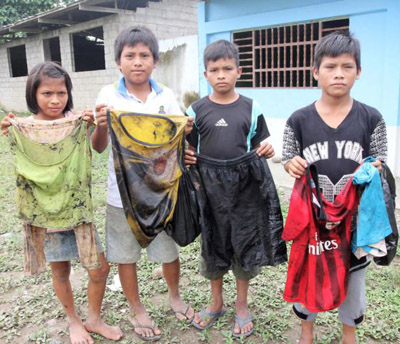 Awajun children in the community of Nazareth, at the confluence of the Chiriaco and Maranon rivers in northern Peru, show the clothes they wore -- with no protective equipment -- to scoop oil out of water near their community after a pipeline break. (CNS photo/Barbara Fraser) See PERU-OIL-SPILL-SCHOOL Feb. 24, 2016.
