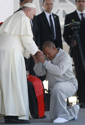 A prisoner kneels before Pope Francis during the pope's visit to Cereso prison in Ciudad Juarez, Mexico, Feb. 17. (CNS photo/Paul Haring)