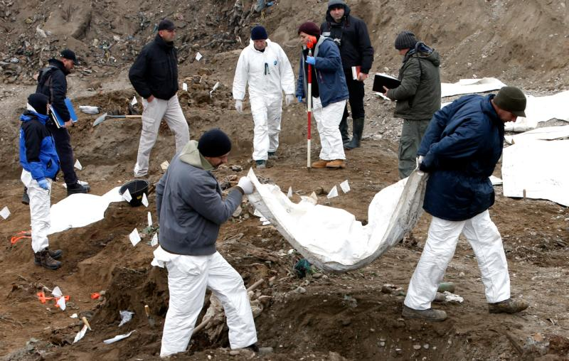 Forensic experts exhume bodies from a mass grave in Kozluk, Bosnia, in this Dec. 15, 2015, file photo. Msgr. Ivo Tomasevic, secretary-general of the Bosnian bishops' conference, called for equal rights for all religious and ethnics groups if the conditions of the 1995 agreement that ended more than three years of war are to be fully realized. (CNS photo/Fehim Demir, EPA)