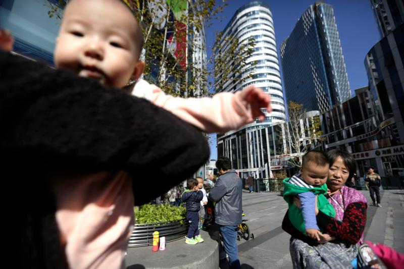 Women carry their babies in a shopping district in Beijing, China, in this Oct. 30, 2015, file photo. (CNS photo/How Hwee Young, EPA)