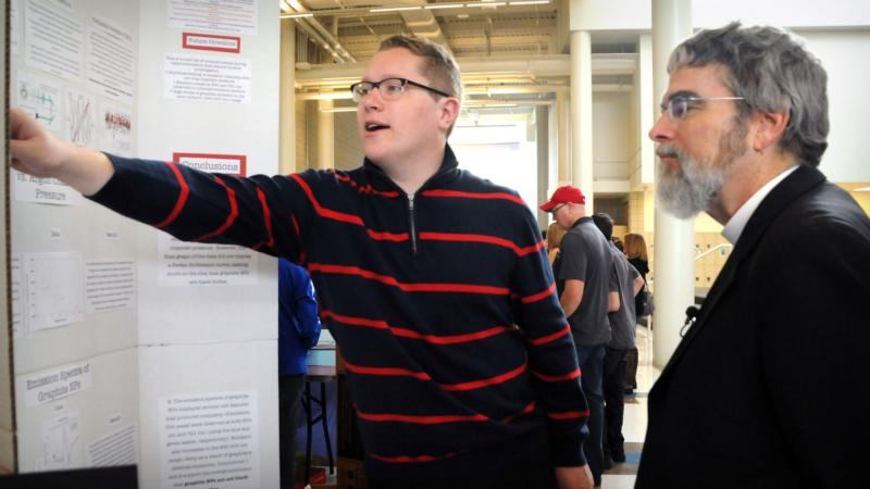 Jesuit Brother Guy Consolmagno, director of the Vatican Observatory, talks with Rex Alley, a senior at Juan Diego Catholic High School in Draper, Utah, about his science experiment on the analysis of graphite nanoparticles, March 13. (CNS photo/Marie Mischel, Intermountain Catholic)