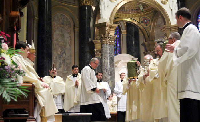The holy oils are brought to the altar for Archbishop Charles Chaput to bless which the priests of the Archdiocese will use in the sacraments of the church throughout the the year.