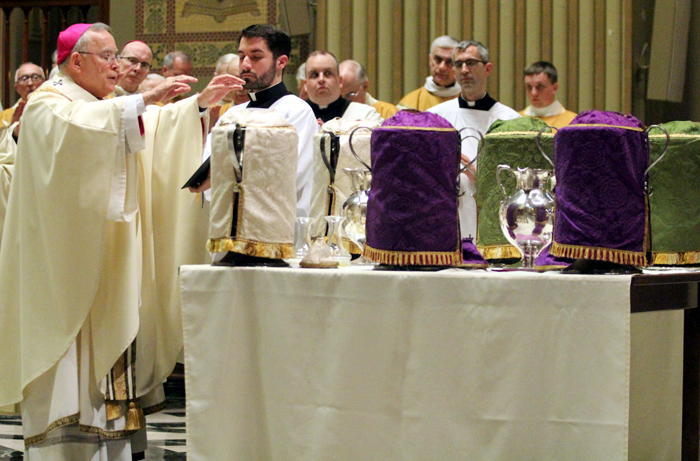 Archbishop Charles Chaput blesses the holy oils to be used by priests in the sacraments of the church throughout the the year.