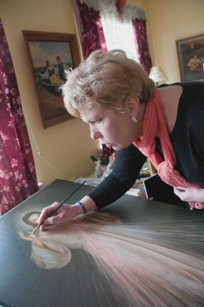 """Susan Pawlukiewicz, a parishioner of Blessed Sacrament Church in Alexandria, Va., accents the wounds of Jesus March 23 in one of 35 Divine Mercy images she brought back from Poland three years ago. She distributes the images, complete with refurbished frames, to area parishes, convents and schools, hoping to help spread """"the idea that mercy and salvation is for all of us,"""" she said. (CNS photo/Katie Scott, Catholic Herald)"""