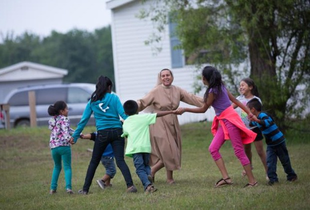 A religious sister dances and sings with children at a camp for migrant farmworkers in the Diocese of Kalamazoo, Mich., in this July 8, 2015, file photo. (CNS photo/Rich Kalonick, Catholic Extension)