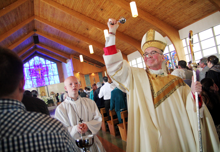 Bishop Timothy Senior sprinkles the faithful at Saitn Rose of Lima Church in North Wales after they renewed their batismal vows on Easter Sunday.