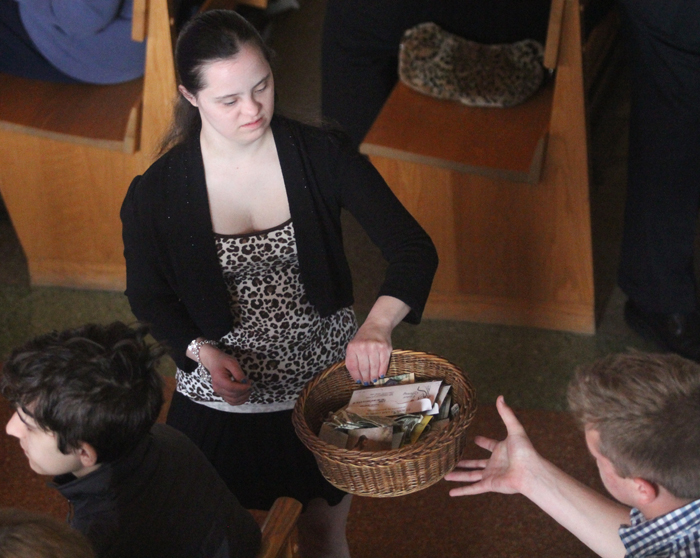 Katie Spencer helps take up the collection at Saint Rose of Lima Church on Easter Sunday.