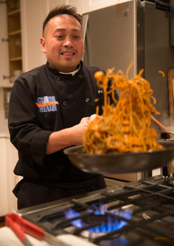 Celebrity chef Father Leo Patalinghug demonstrates how to cook a Lenten seafood pasta meal in his Baltimore kitchen Feb. 24. (CNS photo/Chaz Muth) See FOOD-LENT-PRIEST Feb. 29, 2016.