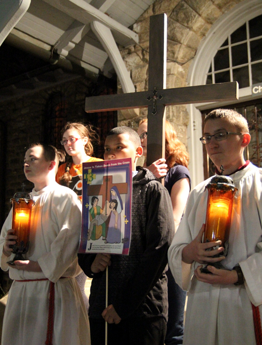 The youth of Saint Charles Borremeo Parish lead a procession from the grotto of their church to Saint Katharine Drexel Shrine for Good Friday.