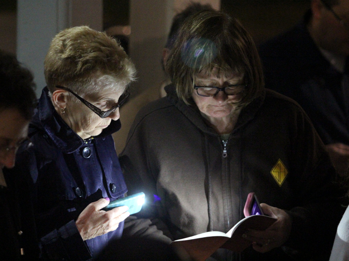 Mary DeLorenzo and Pat Indelicato pray the stations by the light of their cell phones.
