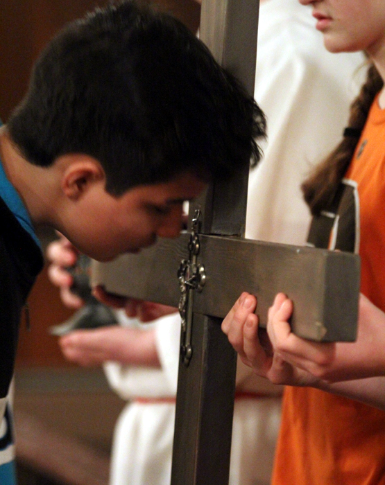 Eric Montero venerates the cross on Good Friday after processing from Saint Charles Borromeo Church to Saint Katharine Drexel Shrine.