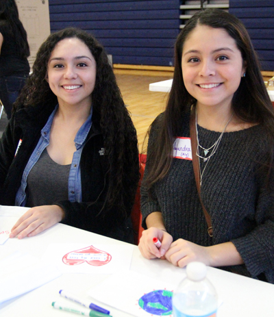 Two friends work together on a service activity at the youth rally. (Sarah Webb)