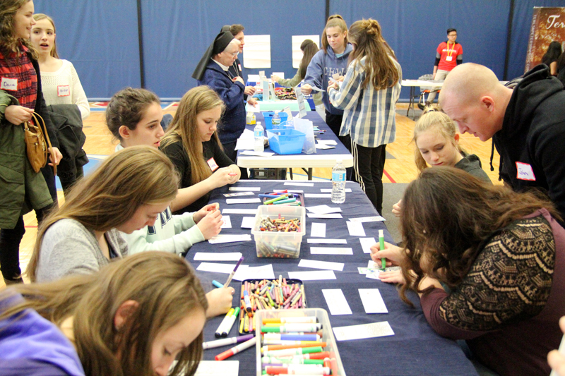 """One activity that involved many teen participants was """"Fill a Bag, Fill a Heart,"""" in which they created decorate bags filled with breakfast items and a personalized written note to be given to the homeless or people in need. (Sarah Webb)"""