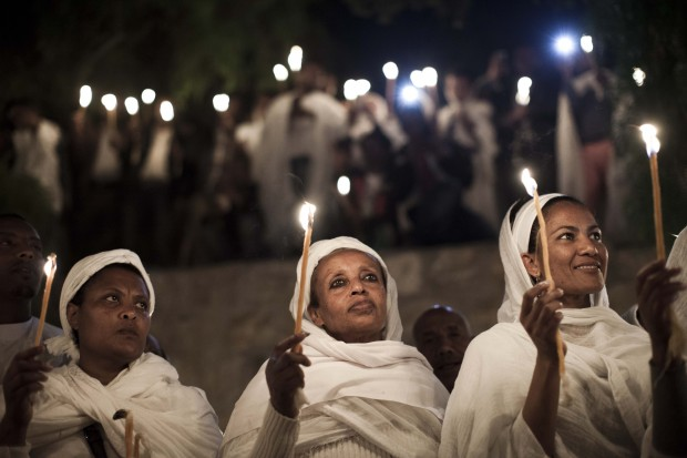 Ethiopian Orthodox Christians light candles and pray during the Holy Fire ceremony in Jerusalem's Church of the Holy Sepulcher in this April 19, 2014, file photo. (CNS photo/Abir Sultan, EPA)