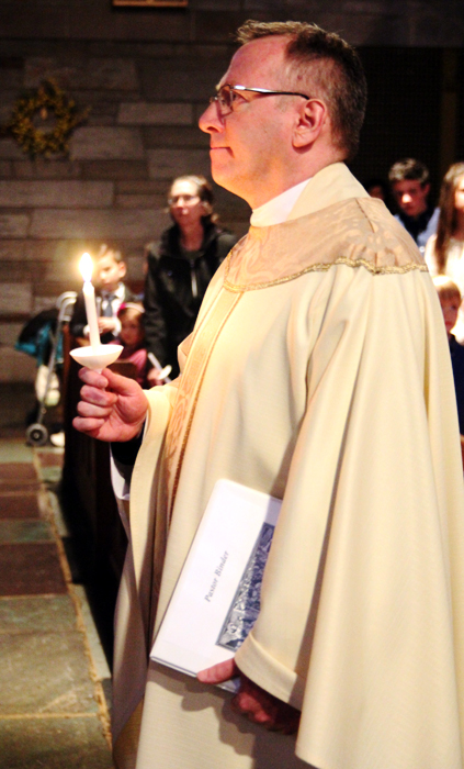 Father Bill Donovan, pastor of Saint Agnes Chuch in West Chester, processes in to the chruch for the Easter vigil mass.