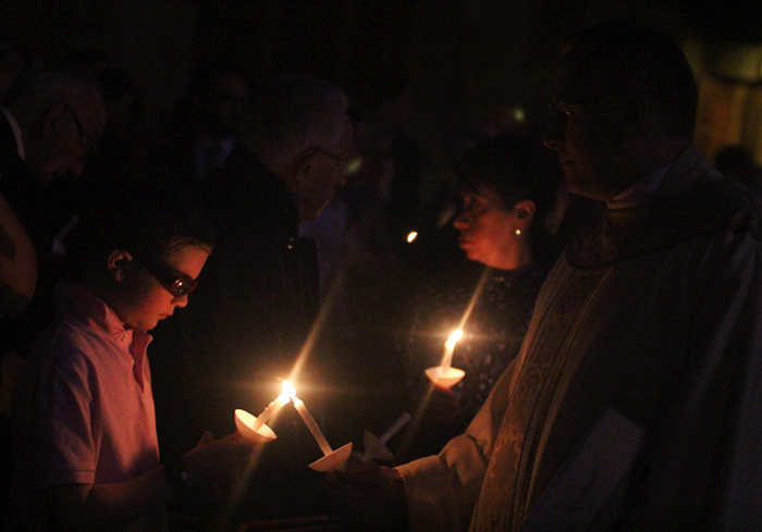 Father Bill Donovan lights the candle of a young man as he processes up the aisle of St. Agnes Church in the evening twilight.