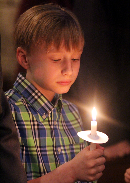 Dominic Zak is fixed on the light of his candle which was lit from the Easter candle.