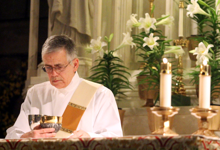 Deacon Francisco Henriquez prepares the altar for the Liturgy of the Eucharist.