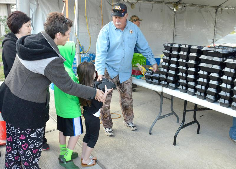 Mike Abbate distributes hot meals at Ascension of Our Lord School in LaPlace, La., Feb. 24. Community members were recovering from a record series to tornadoes to hit the area.(CNS photo/Frank J. Methe, Clarion Herald)