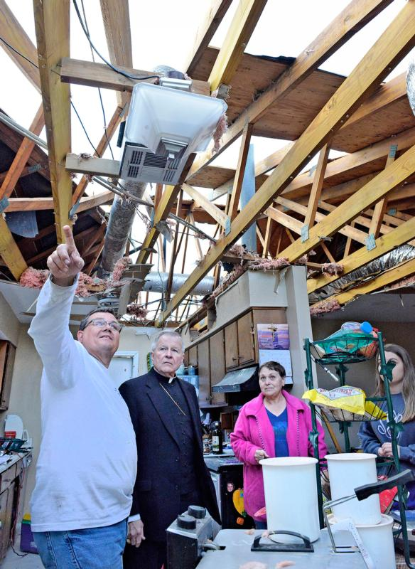 Archbishop Gregory M. Aymond of New Orleans inspects the tornado-damaged home of Dale and Susan St. Pierre of LaPlace, La., Feb. 24. (CNS photo/Frank J. Methe, Clarion Herald)