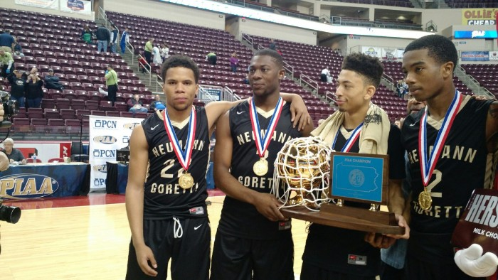 Some members of the Neumann-Goretti boys squad proudly gather around the championship trophy they earned at the PIAA state finals March 18.
