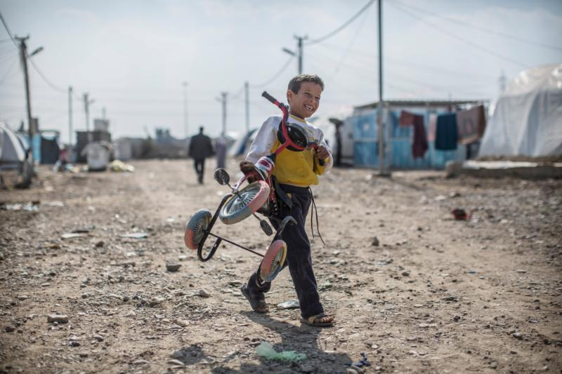 An Iraqi boy smiles as he carries a tricycle in a Baghdad camp for those internally displaced Feb. 3. (CNS photo/Oliver Weiken, EPA)